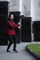 Young Professional videographer holding professional camera on 3-axis gimbal stabilizer. Pro equipment helps to make high quality video without shaking. Cameraman wearing red shirt making a videos.