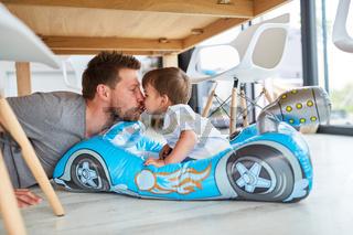 Vater gibt seinem Sohn einen Kuss im Kinderauto