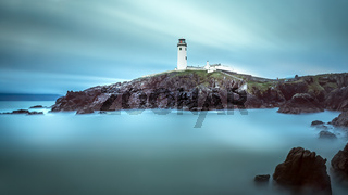 Twilight yields to dawn at Fanad Head Lighthouse. Smudges of clouds and misty water.