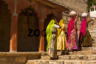 Women carry ceramic pot in a step well, India