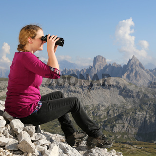 Junge Frau betrachtet die Landschaft in den Bergen