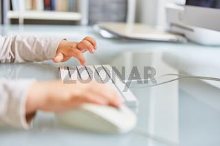 Kleinkind beim Tippen auf Computer Tastatur