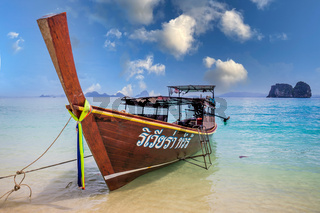 Longtail boat on beach in Thailand with blue sky