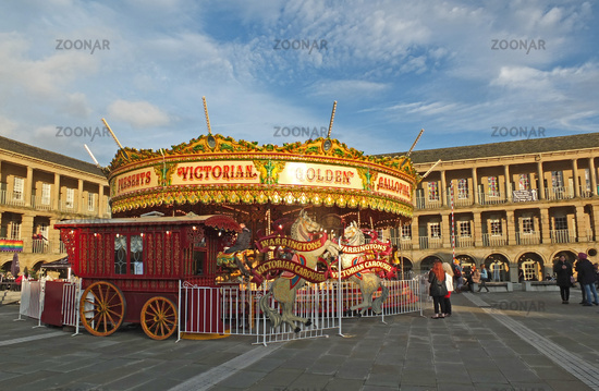people stood watching a vintage carousel in the christmas holidays in the public square at Halifax piece hall west yorkshire