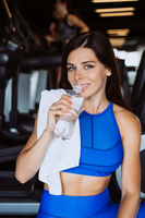 Gorgeous young woman with a towel on her shoulder drinking water from a bottle at the gym