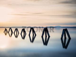 Bollards on lake neusiedlersee at sunset
