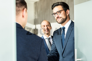 Group of confident business people greeting with a handshake at business meeting in modern office or closing the deal agreement by shaking hands.