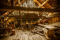 Interior of old wooden shed with scrap wood with sunrays. Old barn.