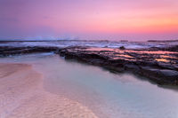 Pretty sunrise over the beach and rock shelf with reflections