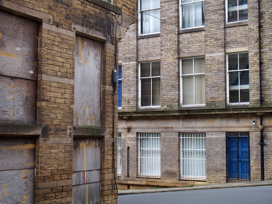 a street corner view of closed and boarded up old abandoned industrial and office buildings in the little germany area of bradford