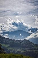 Landschaft in Südtirol. Ein Dorf vor einem Bergpanorama bei Gegenlicht