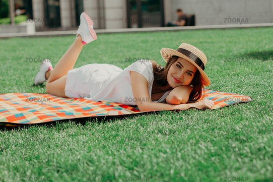 A European Girl In A Straw Hat Relaxed On A Mat In The Park.