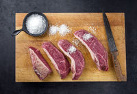 Raw dry aged wagyu cap of rump beef sliced for picanha barbecue skewer with salt offered as top view on a wooden rustic cutting board