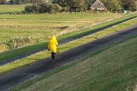 Frau läuft am Hochwasserdamm bei Westerhever | Woman is walking on the flood embankment by Westerhever