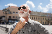 Old man cleaning neck and sweat with wet wipes outdoor on hot summer day