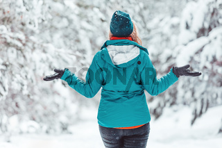 Woman standing in snow among pine forest with snow falling