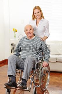 Frau mit ihrem alten Vater im Rollstuhl