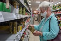 Seniorin mit Mundschutz beim einkaufen im Supermarkt