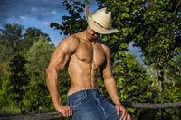 Sexy farmer or cowboy next to hay field