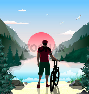 A man with a bicycle on the shore of a mountain lake