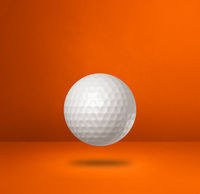White golf ball on a orange studio background