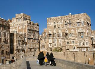 veiled women walking  in sanaa old town in yemen