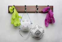 Gloves and respirator masks hanging on clothes rack