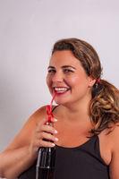 Frau trinkt lachend aus einer Flasche