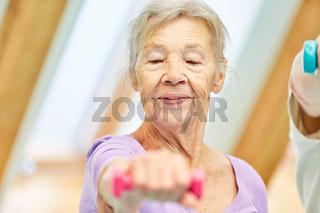 Alte Frau als Seniorin mit Hanteln beim Rehasport