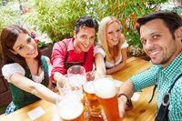 Freunde in Bayern im Biergarten prosten sich zu