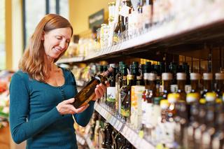 Frau kauft Flasche Ölovenöl im Supermarkt