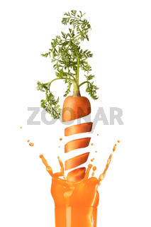 Falling slices of cut carrot to a glass of juice.