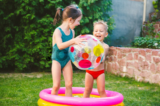 Two children with beach ball at swimming pool. Joyful kid playing in inflatable pool backyard. Little kids at swimming pool on sunny day. Colorful swimming pool ball. Healthy babies summer activity