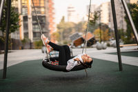 Young woman rides on a swing at the playground.