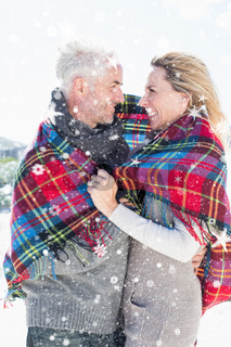 Composite image of happy couple wrapped up in blanket standing on the beach