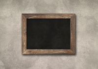 Old rustic black board isolated on a concrete background