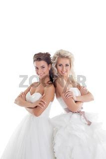 Nice girlfriends posing in elegant wedding dresses