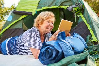 Fröhliche Seniorin vor dem Zelt mit Tablet PC
