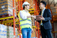 Asian warehouse owner shake hand with warehouse engineer.