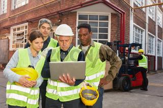 Industrie Arbeiter Team mit Computer vor Fabrik