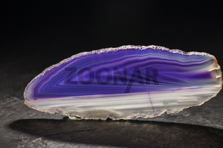 Violet and white striped agate slices on a slate