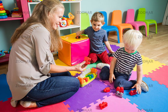 The woman educator makes up a constructor with little boys