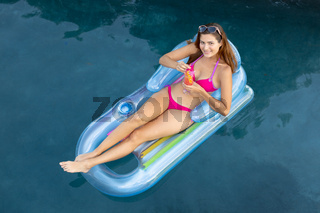 Young woman relaxing in the swimming pool