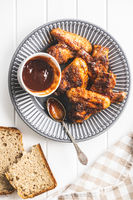 Grilled chicken wings on plate with BBQ sauce.