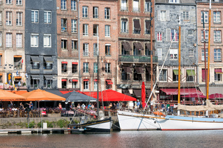Harbor of historic city Honfleur with manoeuvring sailing ship