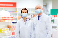 apothecaries wearing medical masks at pharmacy