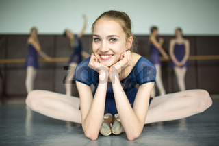 Young ballerina sitting on the floor cross-legged and smiling. A