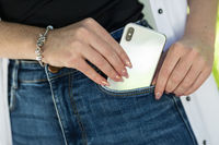 Female hand with beautiful bright design of manicure nails putting modern smart phone in blue jeans pocket