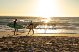 Old couple with surfboard at the beach