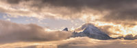 Foggy clouds, mountain top and sun glow in evening sky view